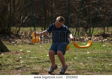 Lonely Down Syndrome Boy On Swing
