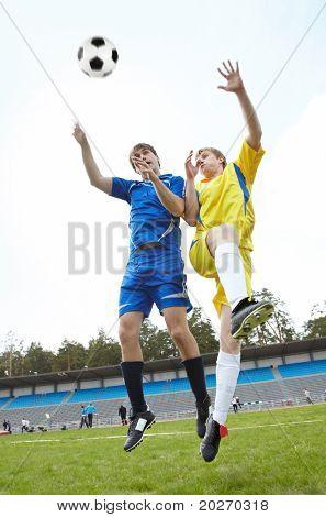 Zwei Fußballer springen und Ball auf Rasen während Spiel suchen