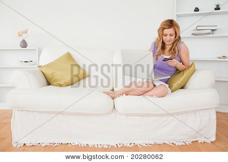 Beautiful woman sitting on a sofa is going to make a payment on the internet while sitting on a sofa in the living room