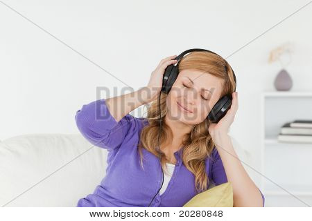 Pretty red-haired woman listening to music and enjoying the moment while sitting on a sofa in the living room