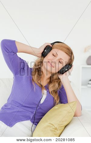 Portrait of a pretty red-haired woman listening to music and enjoying the moment while sitting on a sofa in the living room