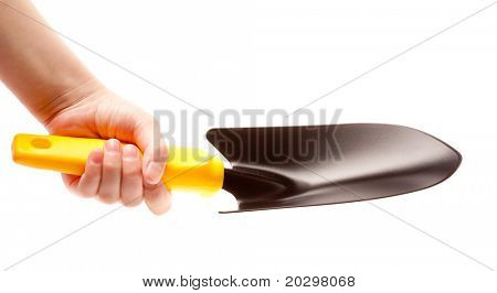 Children's hand holds the trowel, isolated on a white background