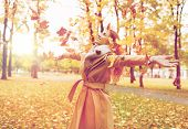 season and people concept - beautiful happy young woman having fun with leaves in autumn park poster