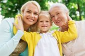 family, generation and people concept - happy smiling woman with daughter and senior mother sitting  poster