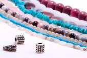 pic of precious stones  - Assorted strings of gem stones beds and spacer beads in front - JPG