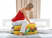 Young woman trying to pack her luggage at home. Luggage overweight concept poster