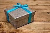 Gift birthday Christmas present concept - silver gift box with blue ribbon on old wooden background poster