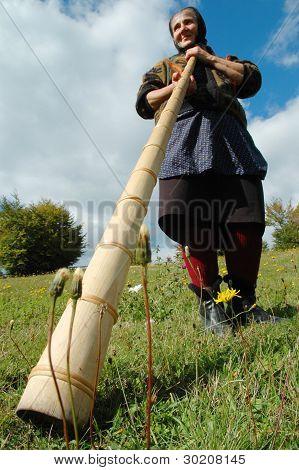 Woman plays the traditional Romanian alpenhorn