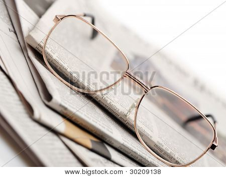Eyeglasses Lie On A Pile Of Newspapers