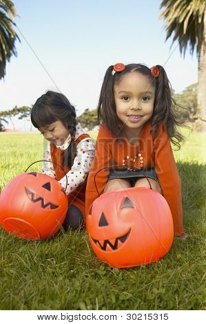 Young girls holding pumpkin buckets
