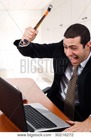 Trabalhador com raiva quebrando seu laptop
