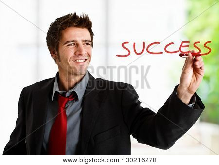 Friendly businessman writing the word Success on the screen
