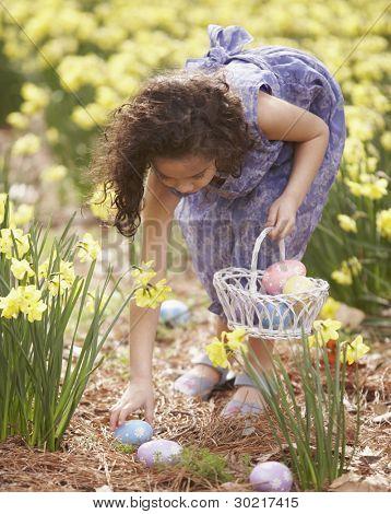 Girl picking up Easter eggs