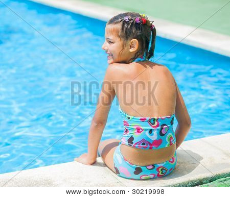 Pretty young girl at pool's edge