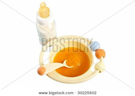 Children Plate With Pumpkin Porridge And Baby Bottle.