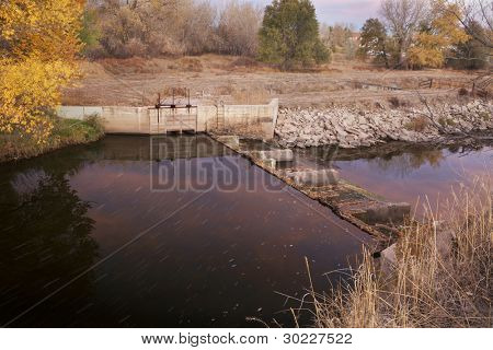 diversion dam with water flowing into irrigation ditch inlet, Cache la Poudre River at Fort Collins, Colorado, fall scenery at dawn