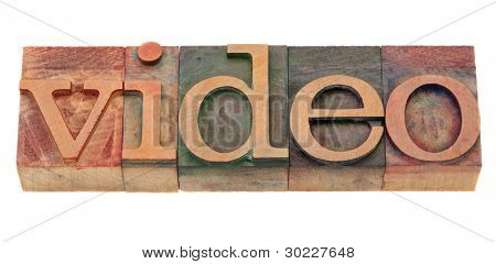video word in vintage wooden letterpress printing blocks, stained by color inks, isolated on white