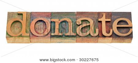 donate - word in vintage wooden letterpress printing blocks, stained by color inks, isolated on white
