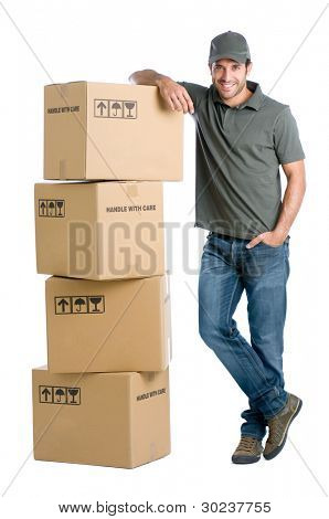Satisfied and proud delivery man leaning on a stack of boxes isolated on white background
