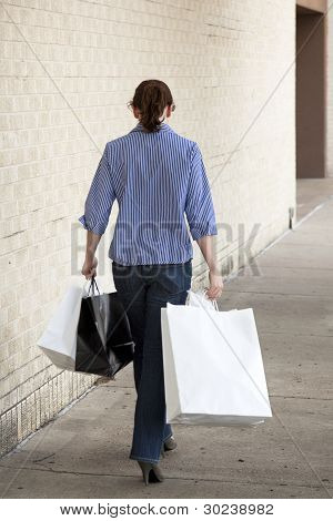 Pretty Woman In Blue Jeans Walking With Shopping Bags At Mall