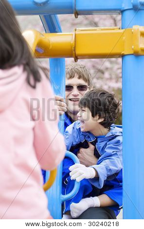 Father Playing At Playground With Disabled Son