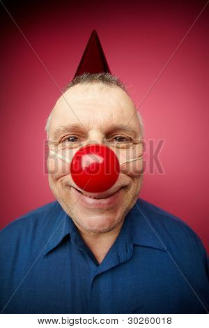 Portrait of a cheerful man with red nose smiling at camera on fool's day