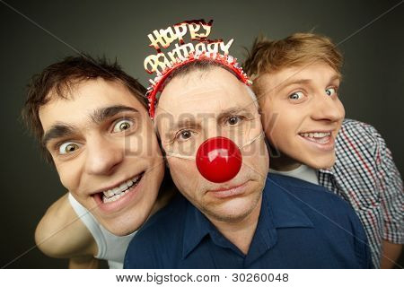 Two guys having fun playing pranks on a senior man celebrating birthday or fool�¢�?�?s day