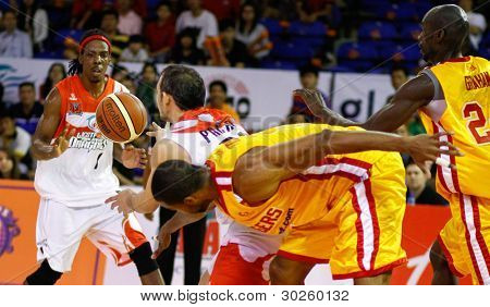 KUALA LUMPUR - FEBRUARY 19: Malaysian Dragons players (white) grab the loose ball from the Singapore Slingers (yellow) at the ASEAN Basketball League match on Feb 19, 2012 in Kuala Lumpur.