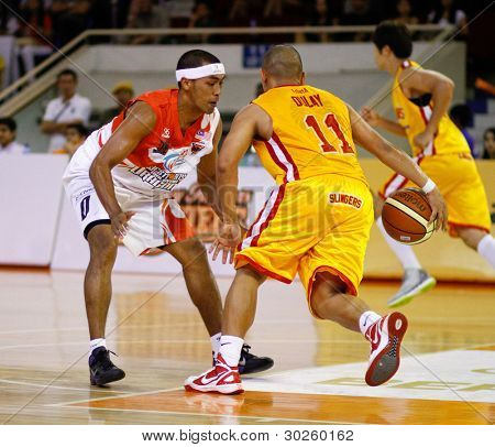 KUALA LUMPUR - FEBRUARY 19: Singapore Slingers' Donald Dulay (11) takes on Dragons Guganeswaran (0) at the ASEAN Basketball League match on February 19, 2012 in Kuala Lumpur. Dragons won 86-71.