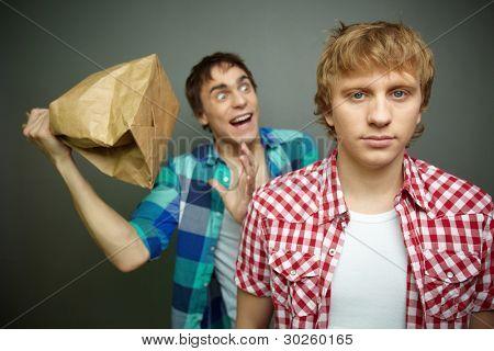 Cara louco, estando prontos para explodir o saco de papel por trás das costas de amigo