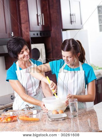 mother teaching teen daughter baking in kitchen