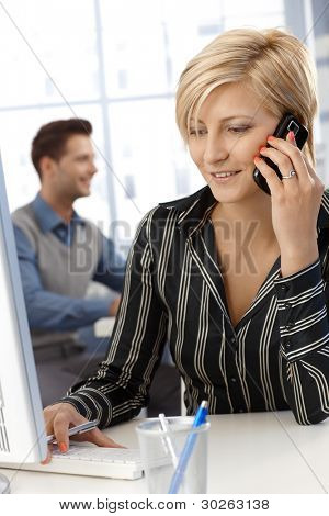 Cheerful businesswoman busy working, using desktop computer and speaking on mobile phone, multitasking.?