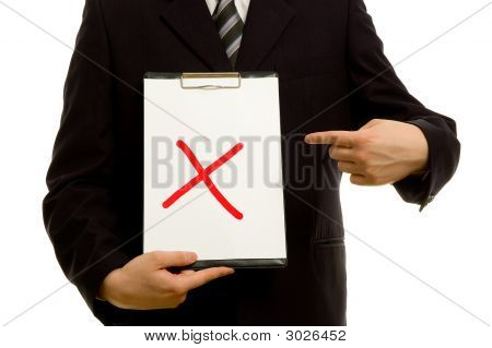 Red X On Clipboard In The Hand Of A Businessman
