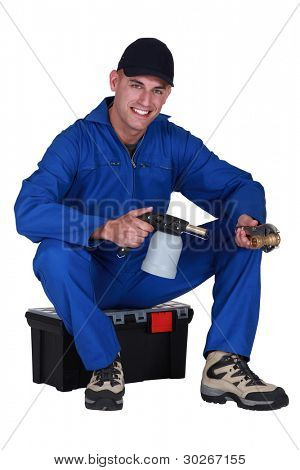 Man sitting on a toolbox with a blowtorch