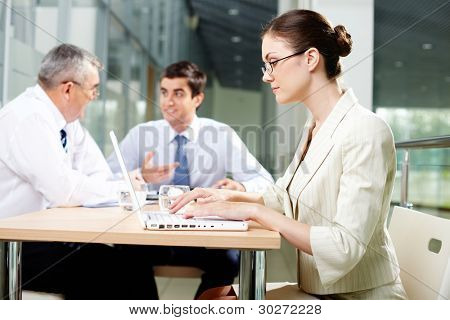 Pretty business lady working on a laptop while her male colleagues discussing business project