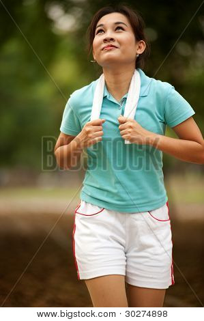 Asian Woman Jogging In The Park  .