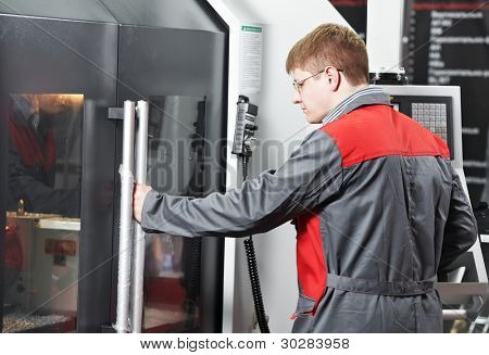 mechanical technician worker at modern cnc metal machining milling center in tool workshop