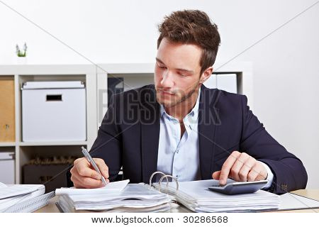 Business man working with calculator and files in office