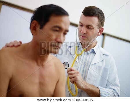 Doctor Working And Visiting Old Man In Clinic