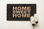 Home sweet home door mat at house entrance with womens sneakers of woman that has just arrived move poster