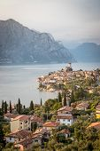 Idyllic Coastline In Italy: Blue Water And A Cute Village At Lago Di Garda, Malcesine, Sunset poster