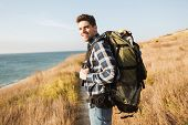 Attractive smiling young man carrying backpack, hiking poster