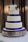 stock photo of three tier  - a modern wedding cake with purple ribbon and 3 tiers - JPG