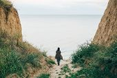 Stylish Hipster Girl Walking To Sea Between Sandy Cliffs With Grass At Sunset. Happy Young Boho Woma poster