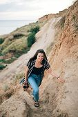 Stylish Hipster Girl Relaxing And Smiling On Sandy Cliff And Holding Photo Camera.  Happy Young Boho poster