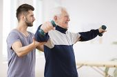Senior Man After Stroke At Nursing Home Exercising With Professional Physiotherapist poster