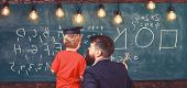 Teacher With Beard, Father Teaches Little Son In Classroom, Chalkboard On Background. Boy, Child In  poster