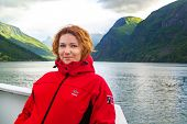Young Beautiful Woman In Smiling Against The Background Of A Norwegian Fjord. Journey Through Norweg poster