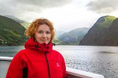 Young Beautiful Woman In A Red Jacket On The Background Of Norwegian Fjord. Journey Through The Norw poster