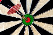 stock photo of fletching  - A dart in the center of a dartboard - JPG